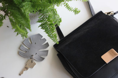 Monstera Keychain on a table with purse and plant